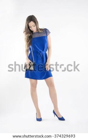 female fashion model wearing blue dress,blue shoes,black purse against light-grey background - stock photo