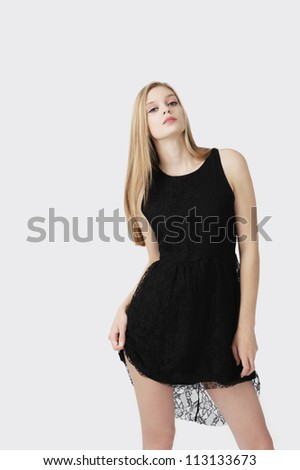 female fashion model with blond hair and black dress posing at grey background - stock photo