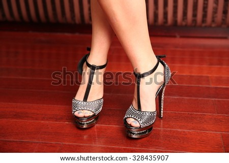 Female feet in black sandals with stones - stock photo