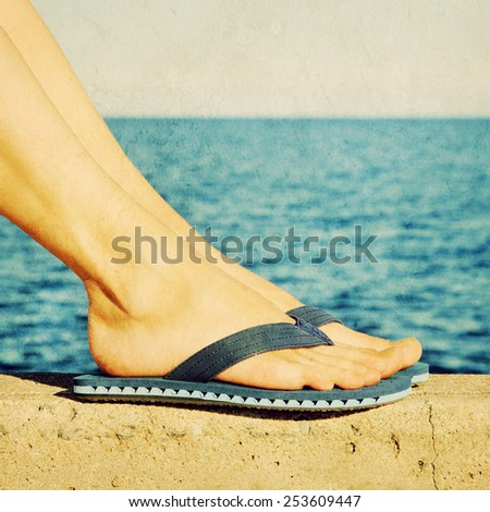Female feet in blue flip-flops with see in the background. Retro styled, aged photo. - stock photo