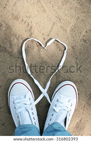 Female feet in gum shoes on sand background - stock photo