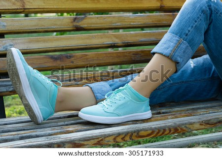 Female feet in jeans and sports shoes on a bench close-up. Girl resting on a bench after a walk in the park. - stock photo