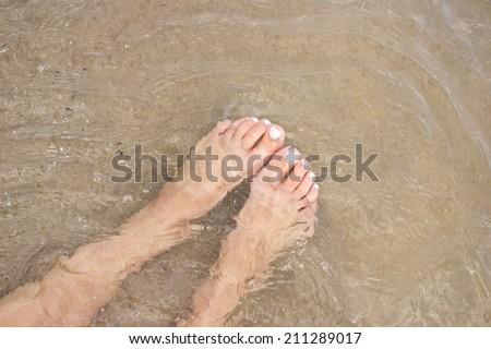 Female feet in water on beach. - stock photo