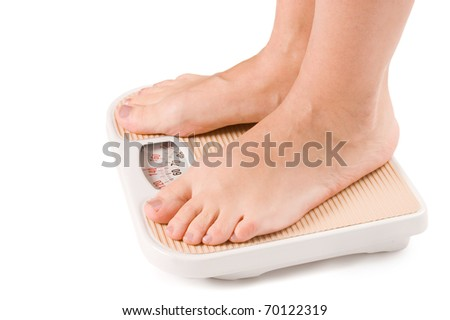 Female feet on scales isolated on white - stock photo