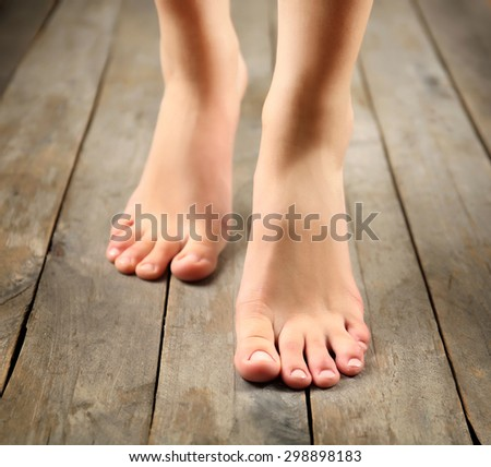 Female feet on wooden background - stock photo