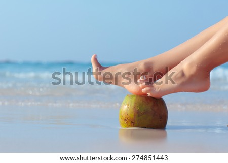Female feet propped on coconut on the beach, blue sea background - stock photo