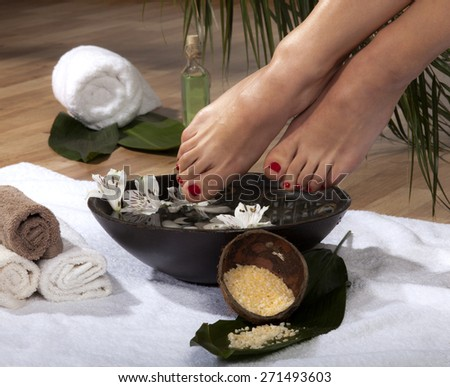 Female feet soaked in spa bowl with flowers and rocks. - stock photo