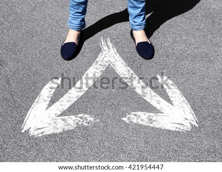 Female feet standing on road with white arrows - stock photo