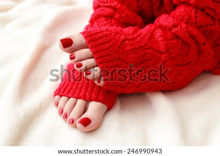 Female feet with a pedicure in red socks - stock photo
