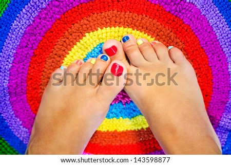 Female feet with color pedicure on a colorful rug - stock photo