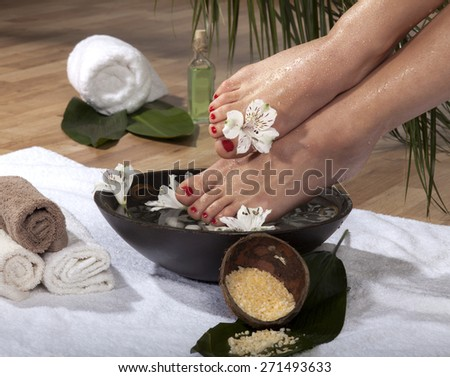 Female feet with drops of water soaked in spa bowl with flowers and rocks. - stock photo