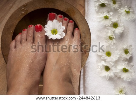 Female feet with drops of water, spa bowl, towel and flowers. - stock photo
