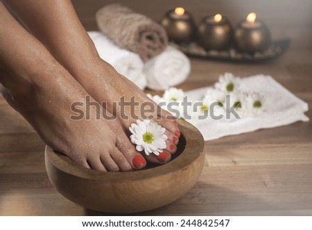 Female feet with drops of water, spa bowls, towels, flowers and candles. Special lighting effect. - stock photo