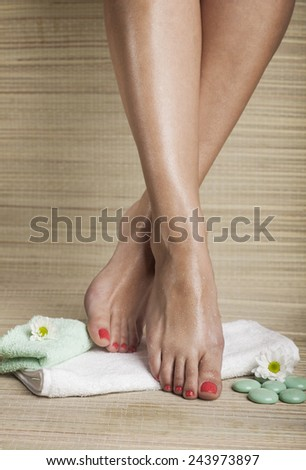 Female feet with drops of water, towel, flowers and spa rocks. - stock photo