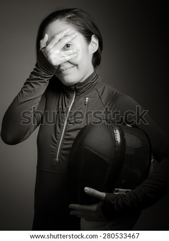 Female fencer peeking through hands covering face - stock photo
