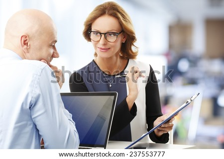 Female financial advisor giving advise to sales man while sitting at office. Teamwork at office.  - stock photo