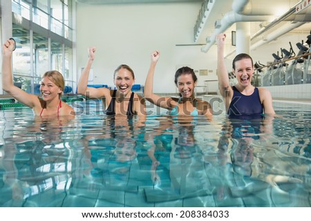 Female fitness class doing aqua aerobics and cheering in swimming pool at the leisure centre - stock photo