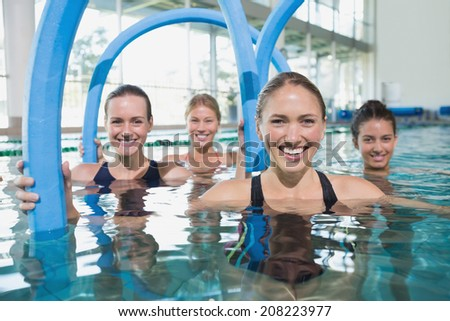 Female fitness class doing aqua aerobics with foam rollers in swimming pool at the leisure centre - stock photo
