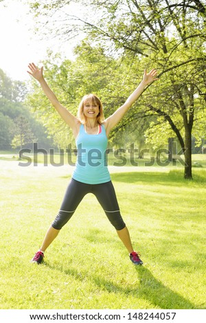 Female fitness instructor doing jumping jacks exercising in green park - stock photo