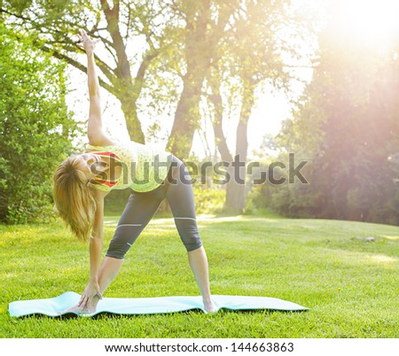 Female fitness instructor doing yoga extended triangle pose outdoors in morning sunshine - stock photo