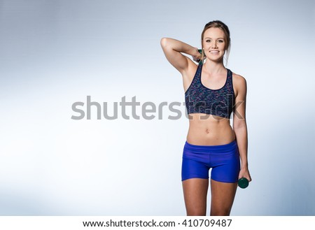 Female fitness model excercising in studio with dunbell weights and doing a floor routine of stretches and lifts on a matt. - stock photo