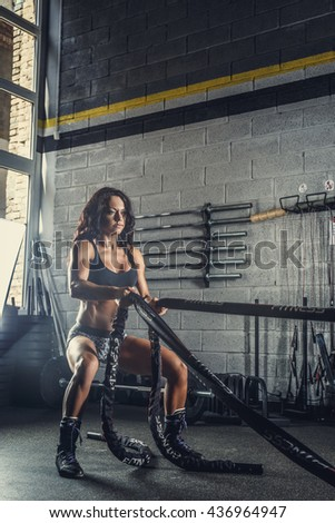 Female fitness model exercising with battle rope in a gym club. - stock photo
