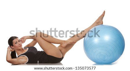 female fitness model exercising with blue ball - stock photo