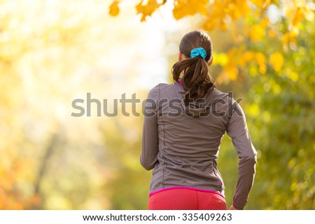 Female fitness model training outside and listening to music. Sport and healthy lifestyle. Shot from behind - stock photo