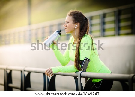 Female fitness sport runner jogging and looking by sea.She is exercising on sunny day and drinking bottle of water. Idyllic view of mountain range is in background. - stock photo