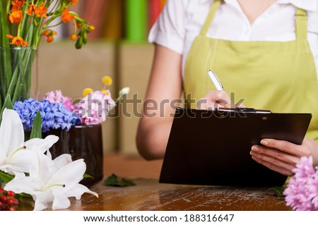 Female florist at work. Cropped image of female florist writing something at note pad while standing at her working place - stock photo