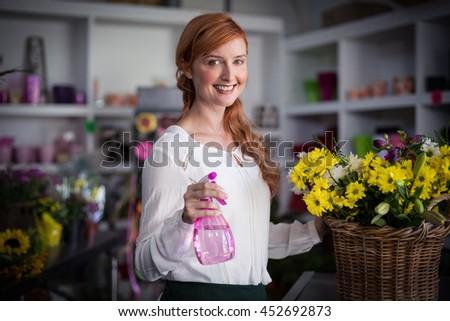 Female florist holding spray bottle in the flower shop - stock photo