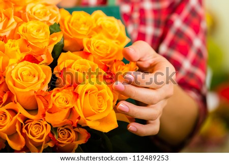 Female florist in flower shop or nursery presenting roses, close-up - stock photo