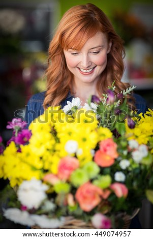 Female florist standing and smiling in the flower shop - stock photo
