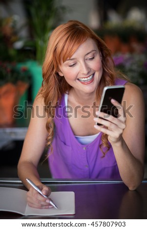 Female florist using mobile phone in the flower shop - stock photo