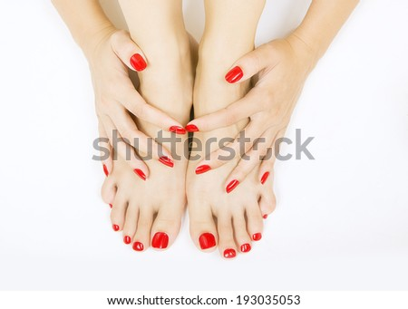 female foots with red pedicure and hands with red manicure - stock photo