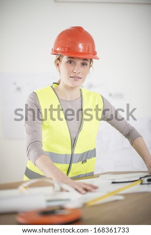 female foreman in his office is reviewing building plans - stock photo