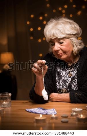 Female fortune teller predicting future with pendulum - stock photo