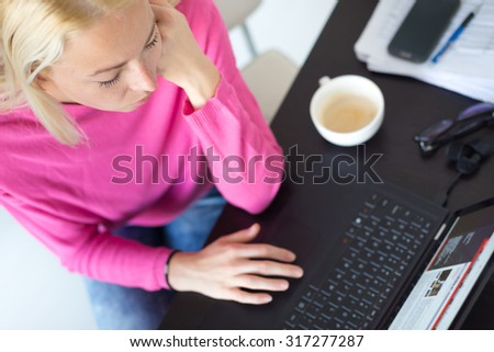 Female freelancer in her casual home clothing remotly working on laptop computer from her home while drinking her morning cup coffee. View from above. - stock photo