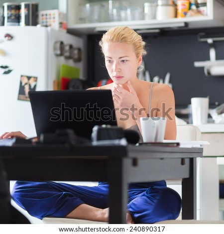 Female freelancer in her casual home clothing working remotly from her dining table in the morning. Home kitchen in the background. - stock photo