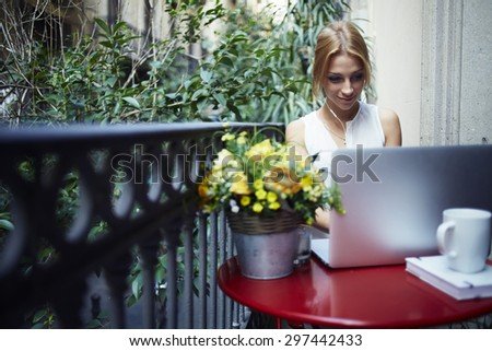 Female freelancer sitting front open laptop computer and listening to music with headphones while enjoying her breakfast,young gorgeous woman relaxing on the terrace balcony looking at net-book screen - stock photo