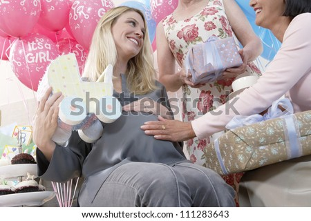 Female friend touching tummy of a pregnant woman at a baby shower - stock photo
