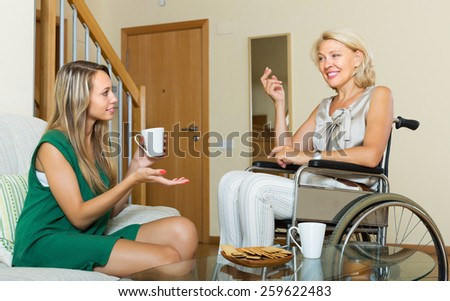 Female friend visiting smiling disabled woman on chair indoor - stock photo