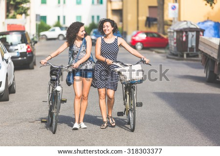 Female friends, a couple or sisters,  holding bikes and walking in the city. They are two women, they are talking and smiling. There are some houses and cars on background. - stock photo