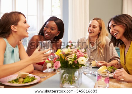 Female Friends At Home Sitting Around Table For Dinner Party - stock photo