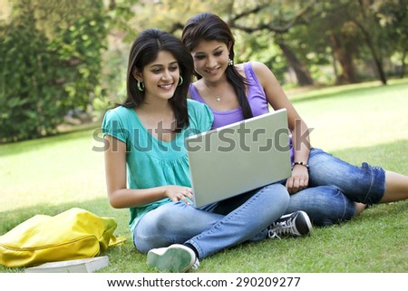 Female friends chatting on laptop - stock photo