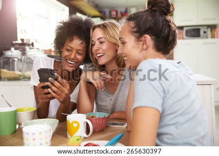 Female Friends Eating Breakfast Whilst Checking Mobile Phone - stock photo