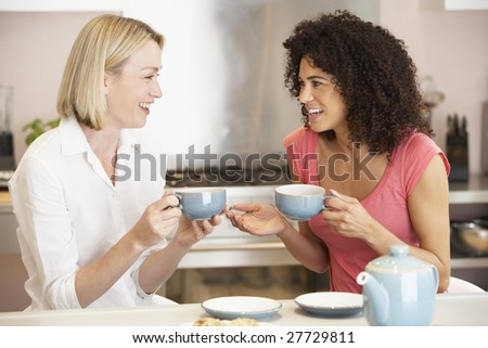 Female Friends Enjoying Tea And Cookies At Home - stock photo