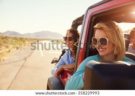 Female Friends On Road Trip In Back Of Convertible Car - stock photo