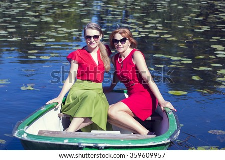 Female friends sailing in the small boat - stock photo