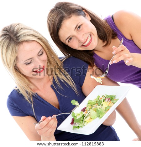 Female friends sharing a plate of salad Two attractive female friends sharing a plate of healthy leafy green salad together isolated on white - stock photo